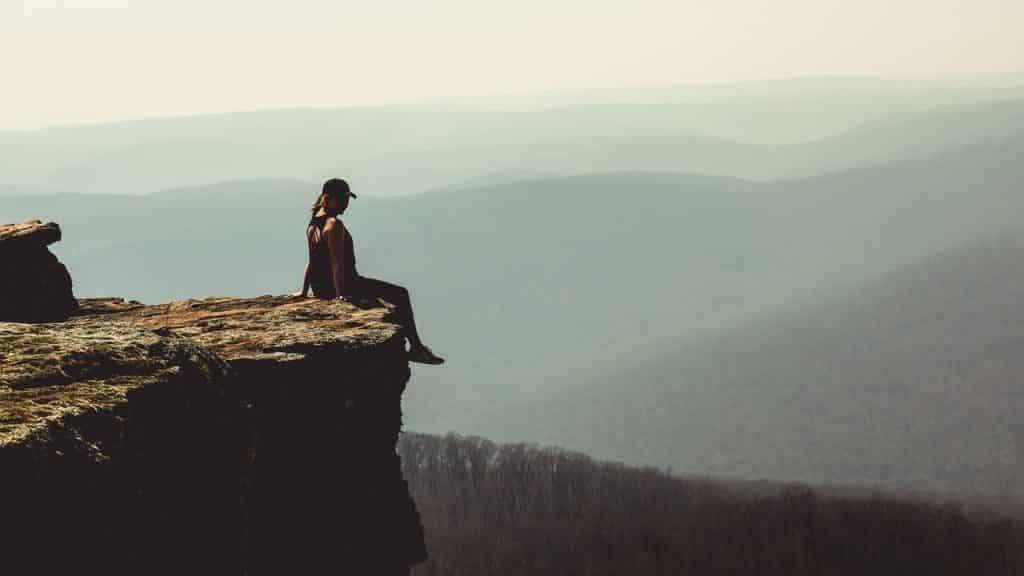 Mulher sentada em pico de montanha.