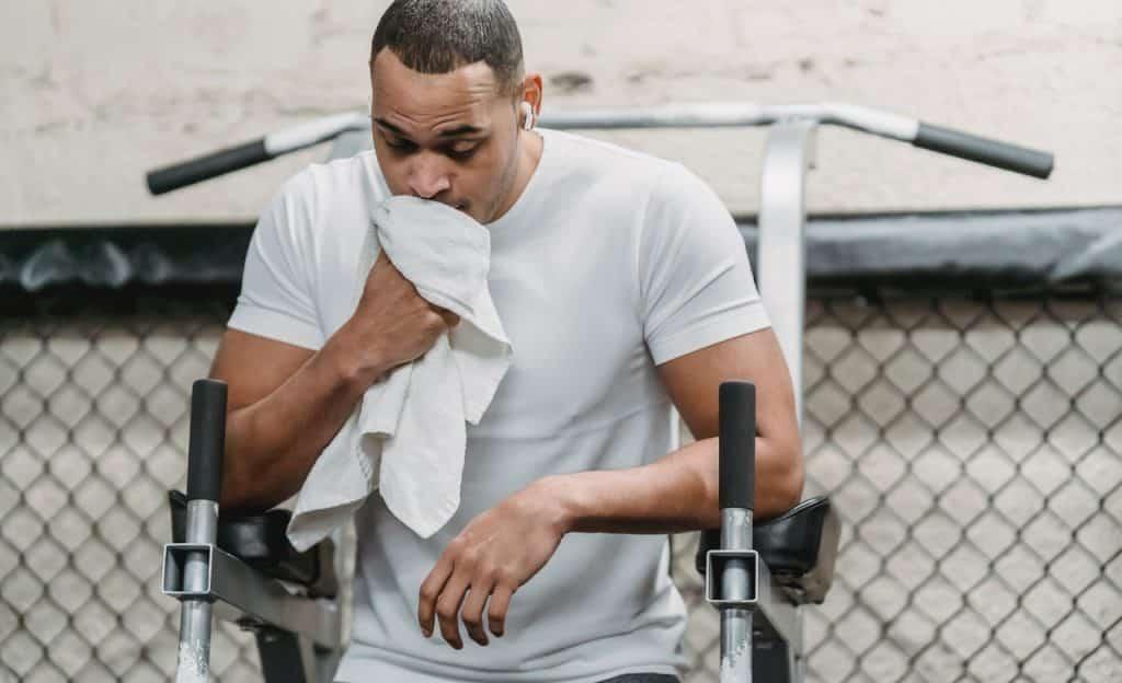 Homem enxuga o rosto com toalha branca. Ele está praticando exercícios físicos.