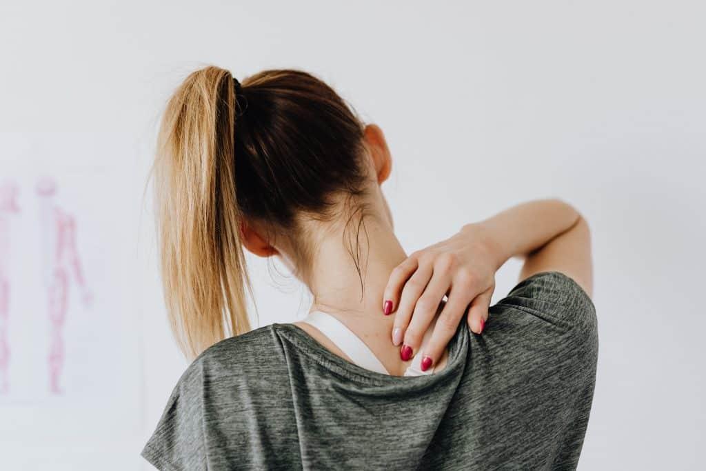 Mulher de cabelos presos em rabo de cavalo pressiona a coluna cervical com os dedos.