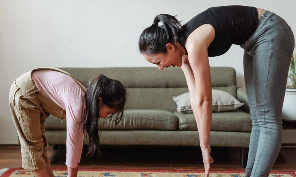Mulher e menina riem enquanto praticam yoga em sala de estar.