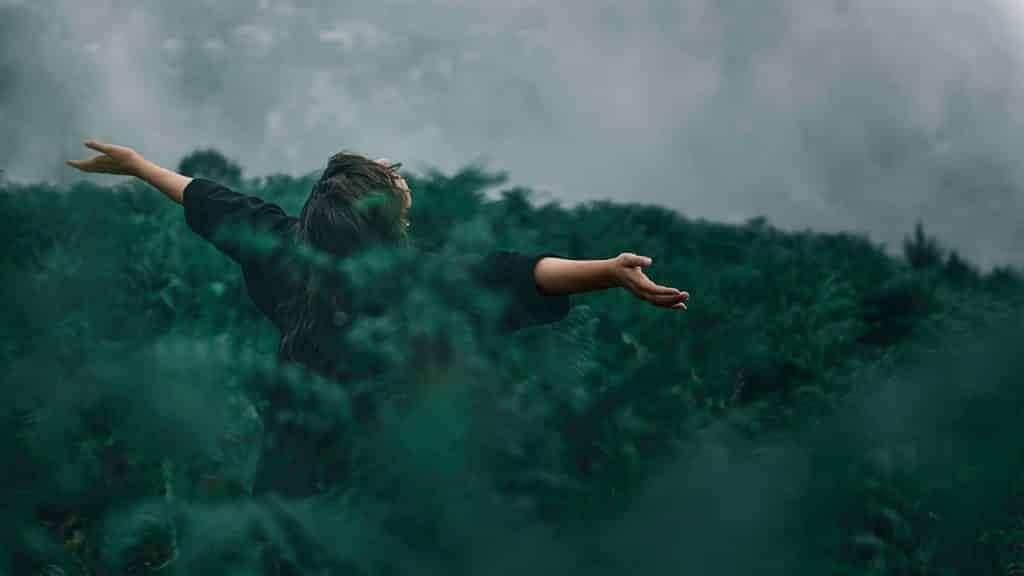 Mulher em cenário externo de campo. Ela está, com os braços erguidos e abertos, entre a plantação alta. Sua cabeça está inclinada para trás.