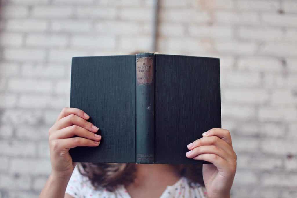 Moça com um livro em frente ao seu rosto