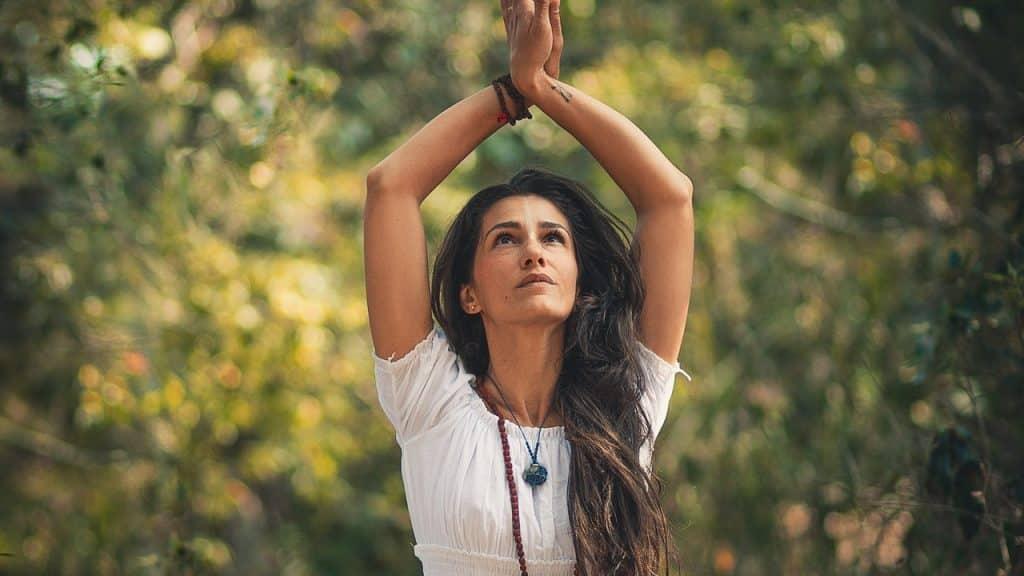 Mulher olha para cima, onde suas mãos se unem, erguidas. Ela está em cenário externo.