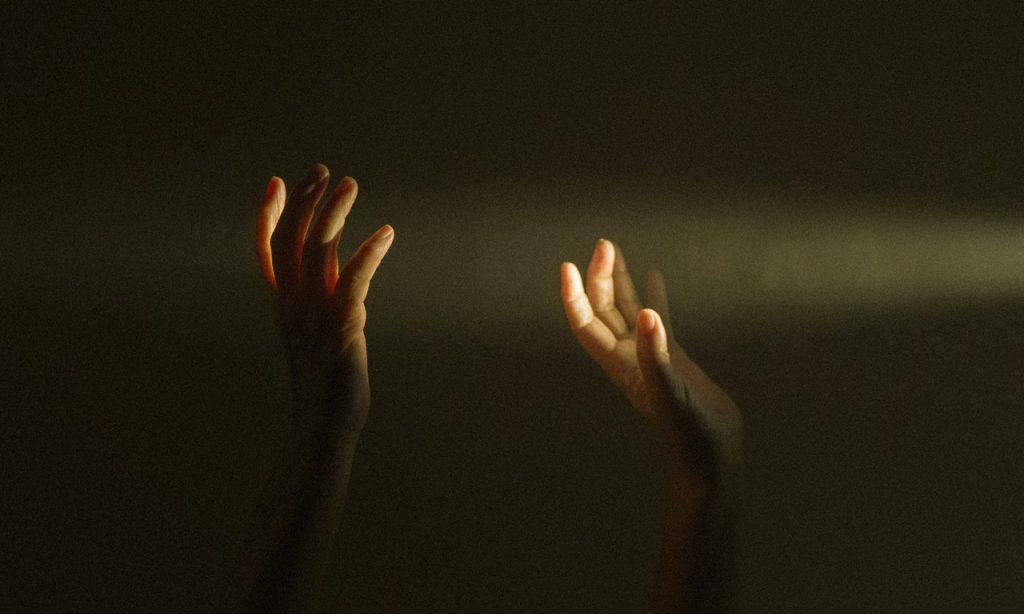 Luz encontra duas mãos erguidas. O cenário é escuro.