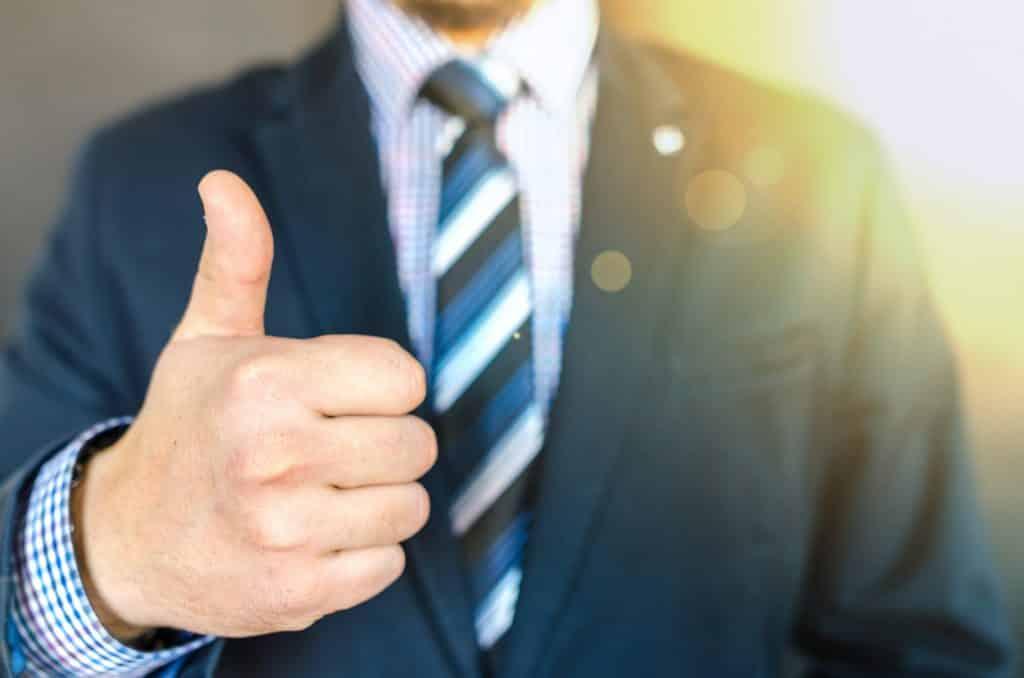 Homem de terno fazendo sinal de positivo com a mão direita
