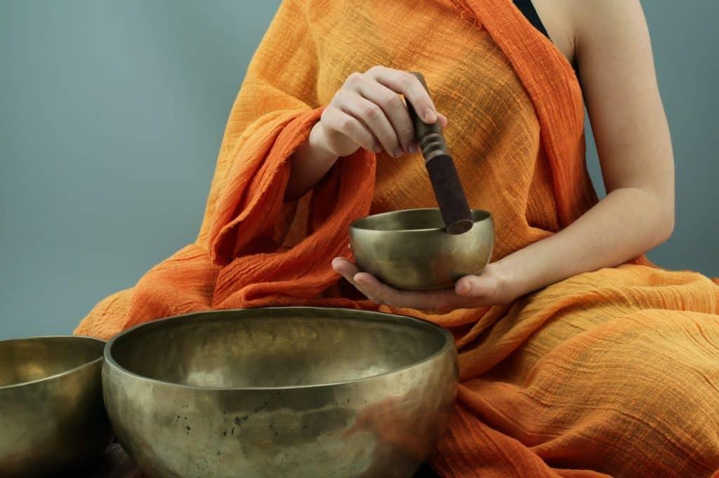 Monge tocando tigela tibetana.