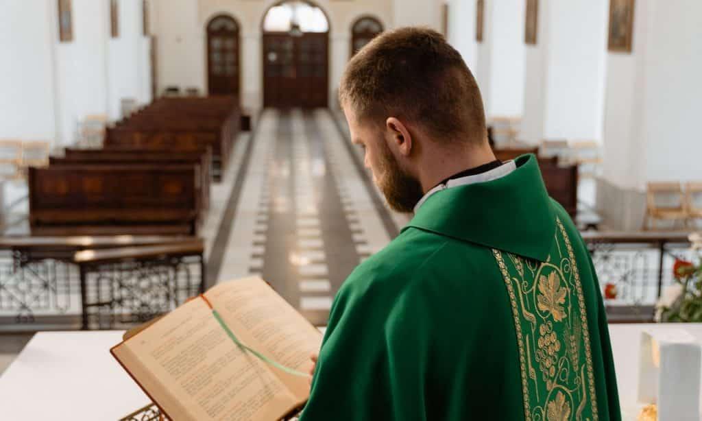 Reverendo lê bíblia em igreja vazia.