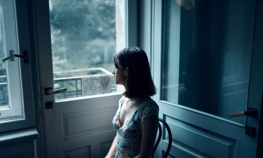 Mulher sentada em cadeira próxima de uma porta com janela. Ela observa o exterior.