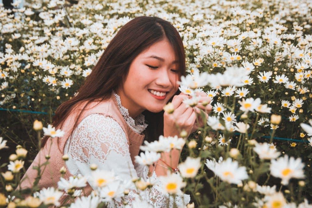 Mulher em um campo de flores sorrindo de olhos fechados