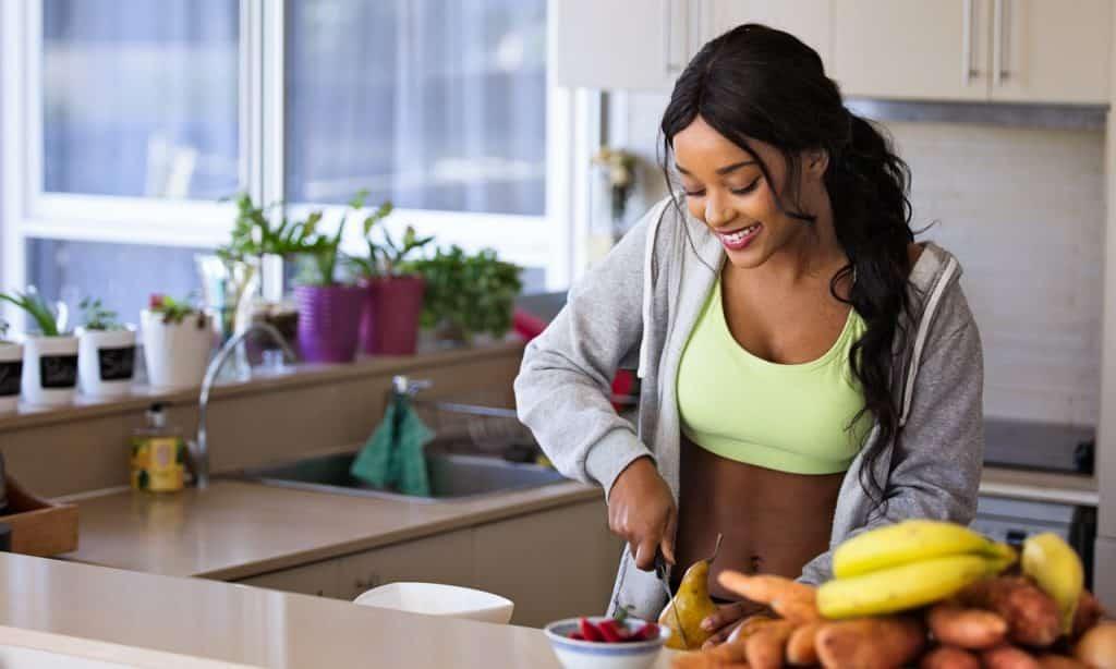 Mulher corta fruta sobre bancada. Ela está em uma cozinha.
