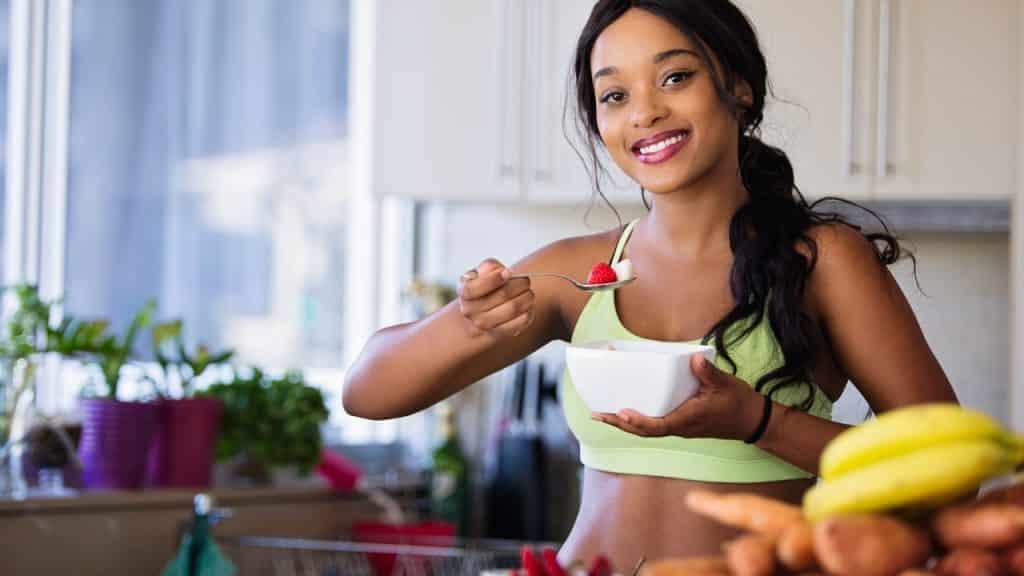Mulher segura uma tigela de porcelana branca e uma colher com frutas. Ela sorri e intenciona comer as frutas. O cenário é de uma cozinha.