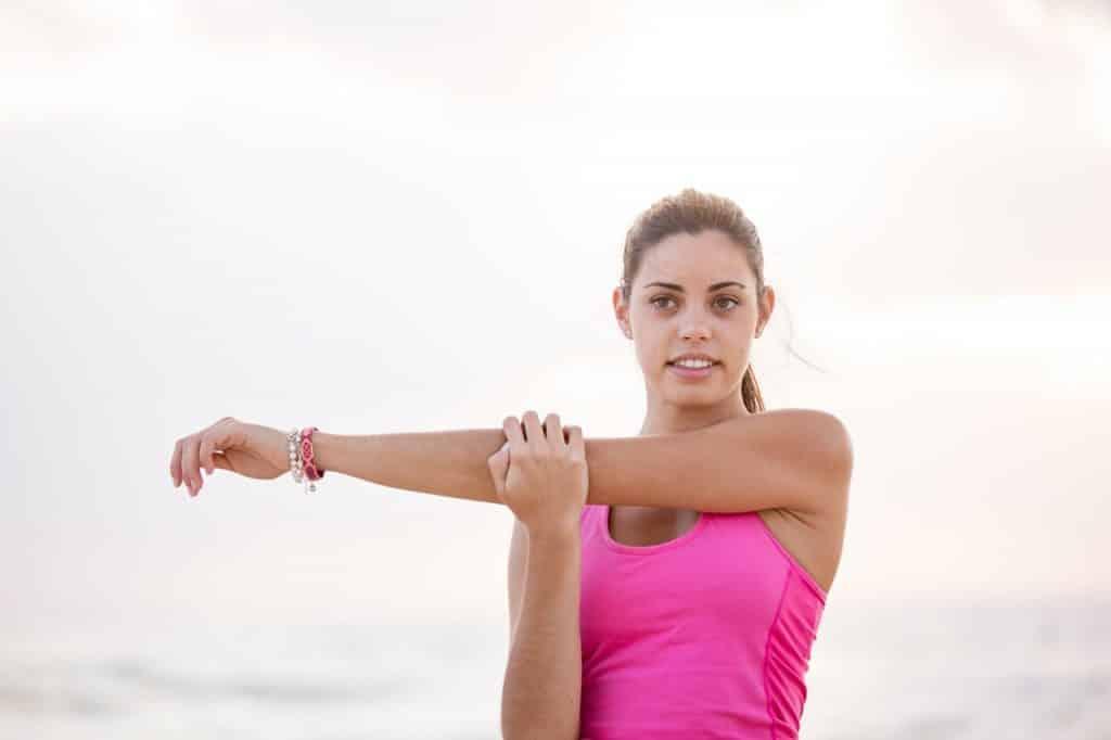 Mulher branca alongando o braço.