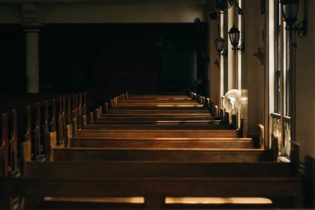 Foto de uma fileira de bancos em uma igreja.