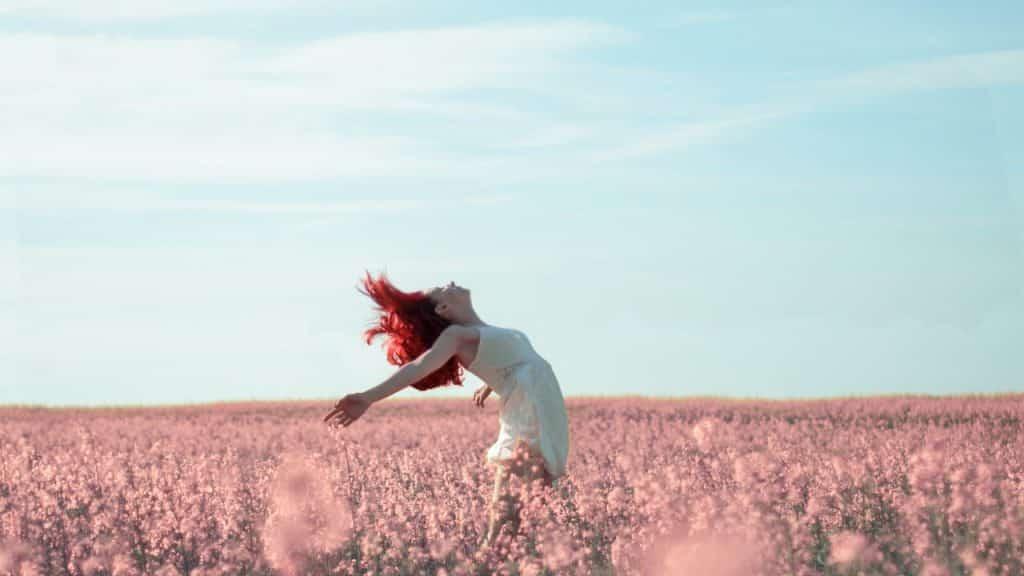 Mulher, com os braços abertos, inclina-se para trás em campo de flores. Seus cabelos estão ao vento.