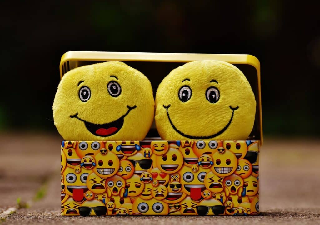 Caixa com duas pelúcias de emojis sorridentes