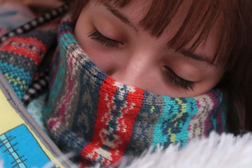 Mulher deitada se aquecendo com cachecol em seu rosto