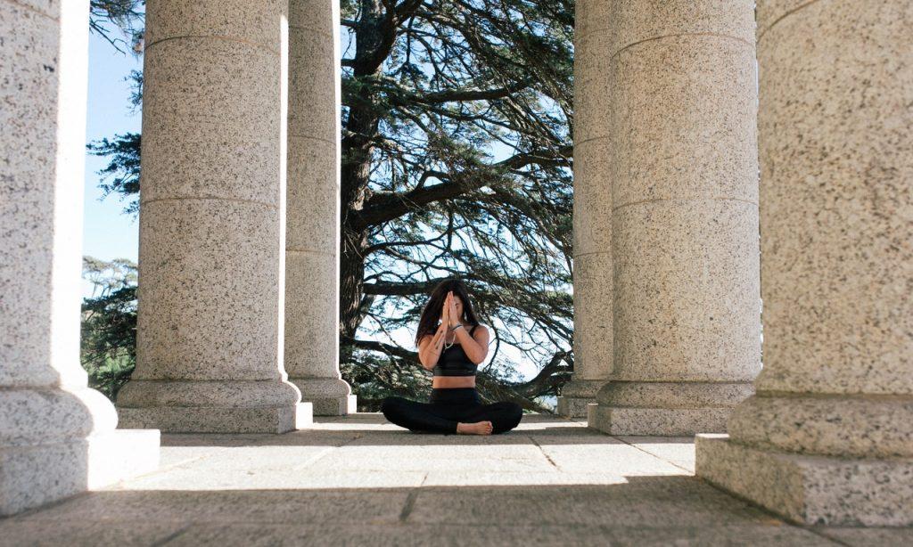 Mulher medita em área externa de colunas de concreto cinza.