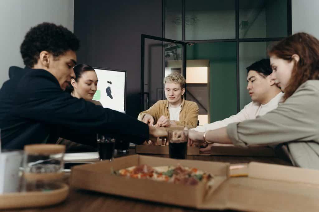Pessoas reunidas comendo pizza