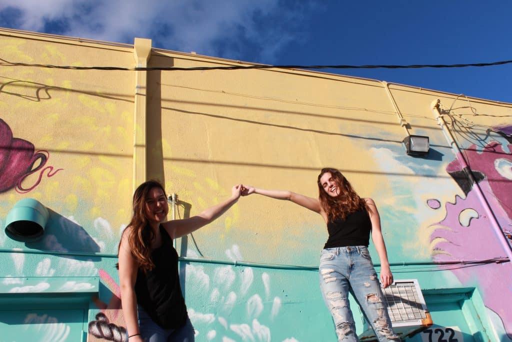 Duas mulheres de mãos dadas e sorrindo na rua