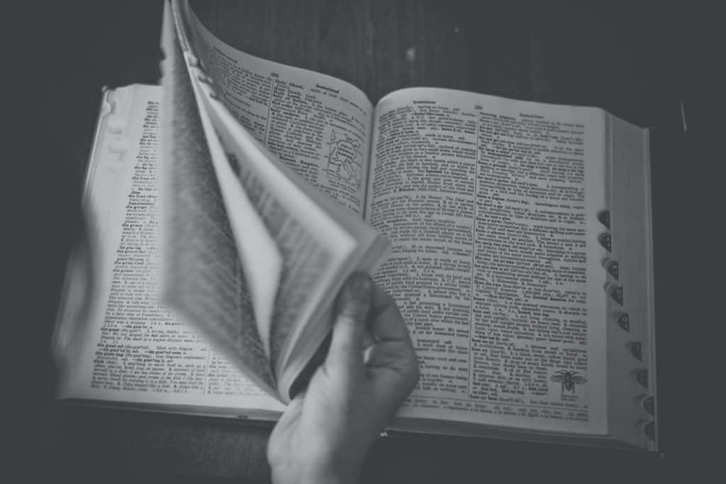 Pessoa passando as páginas de um dicionário