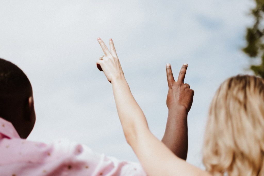 Mulher branca e homem negro com os braços levantados.