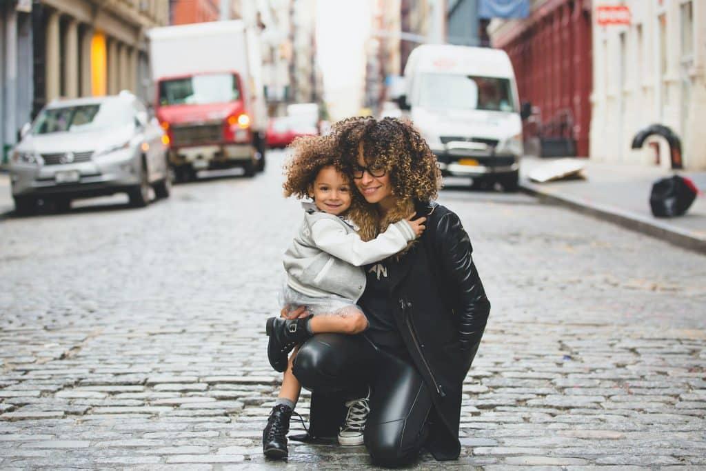 Mulher e menina negras abraçadas.