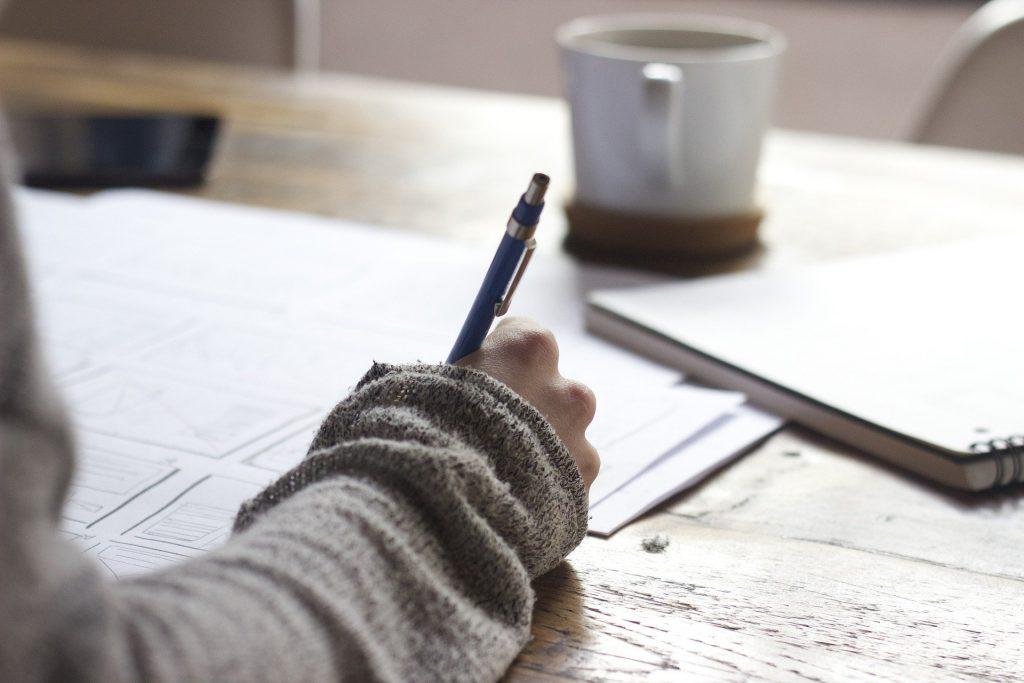 Mão escrevendo em papel sulfite com lapiseira