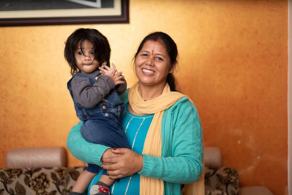 Mulher indiana segurando criança no colo.