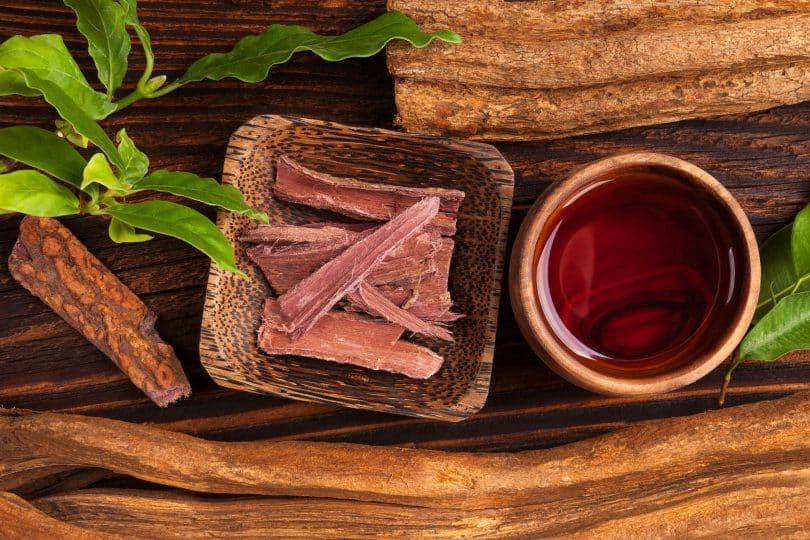 Poção de ayahuasca com casca de raiz na mesa de madeira de cima.
