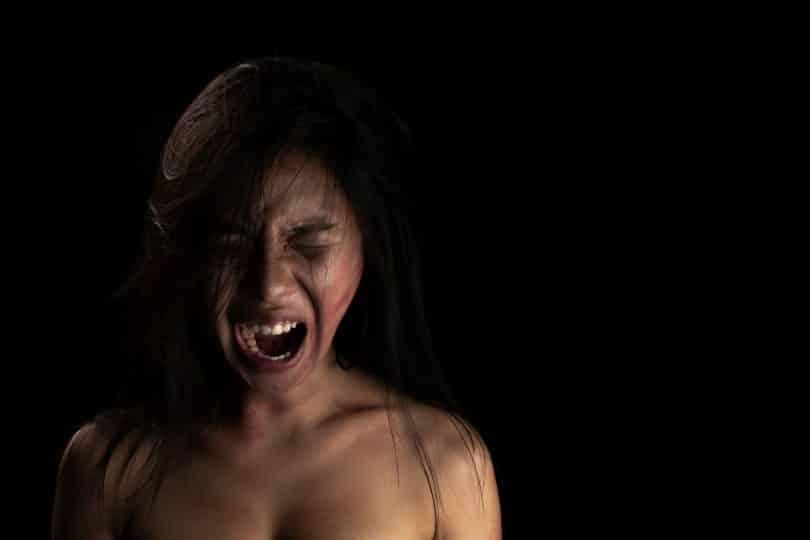 Mulher grita com semblante raivoso.