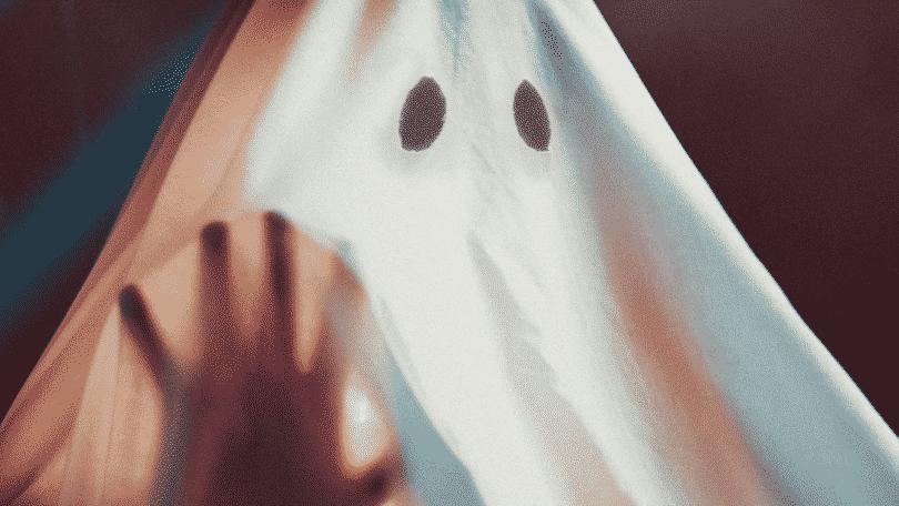 Fantasma de lençol com a mão erguida sobre o pano
