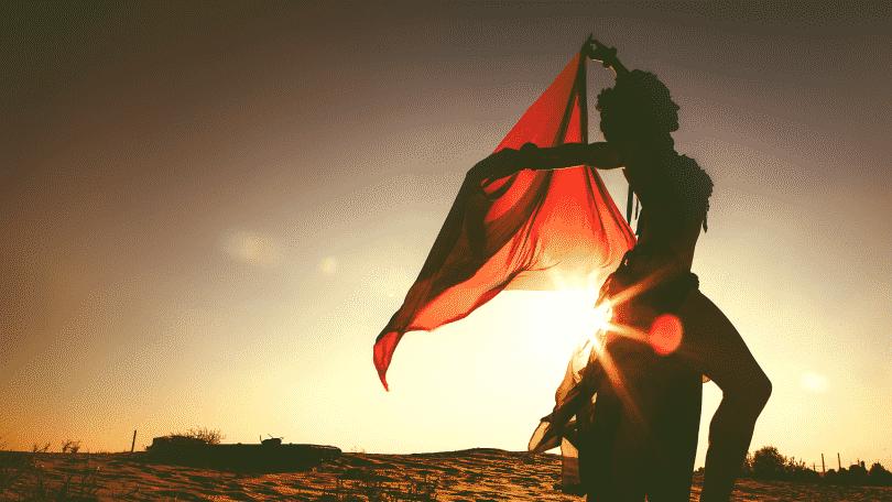 Silhueta de mulher dançando no deserto com lenço vermelho durante por do sol