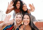 """Mulheres amigas tirando selfie sorrindo fazendo sinal de """"pare"""" com a destra"""