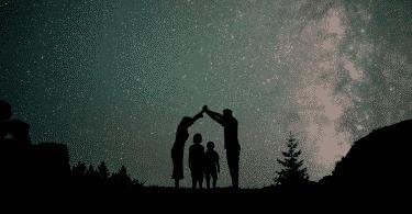 Silhueta de família observando o céu estrelado