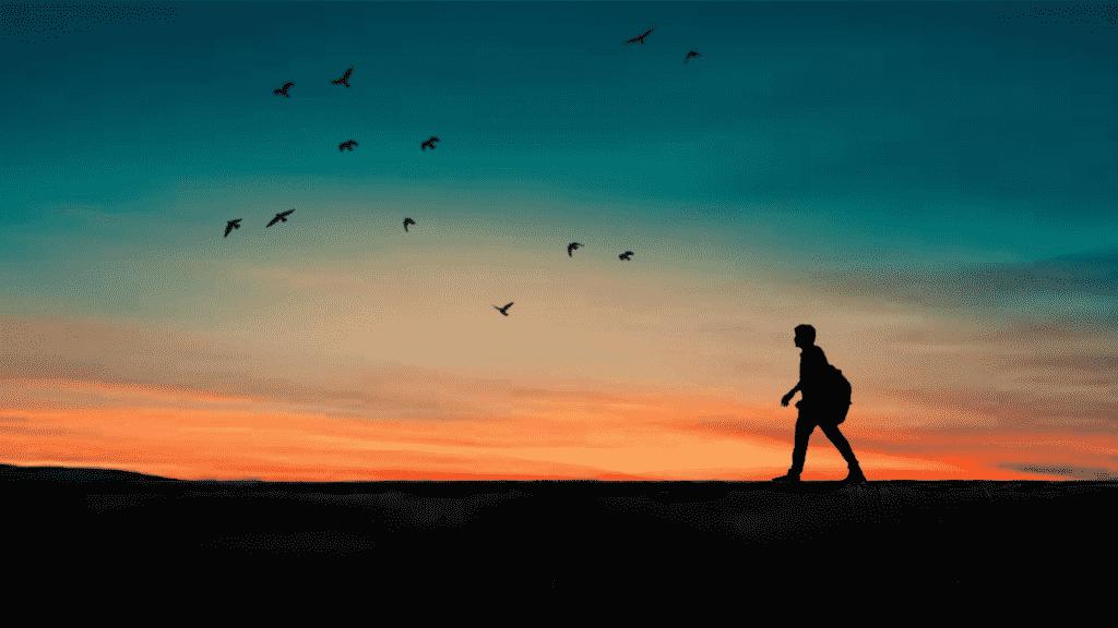 Silhueta de homem caminhando sob o pôr do sol