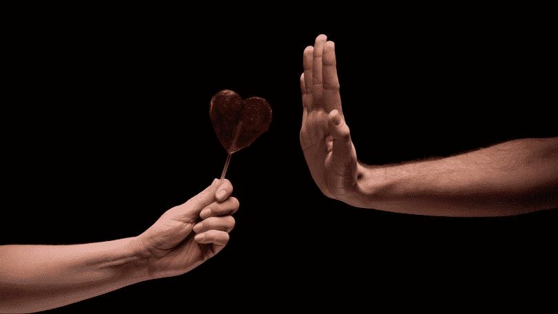 Pessoa recusando um pirulito em formato de coração