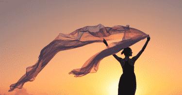 Silhueta de mulher segurando um lenço voando