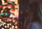 Mulher olhando pensativa para a cidade pela janela