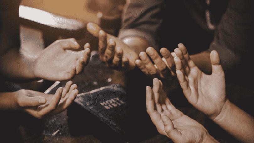 Grupo de oração rezando com a bíblia aberta