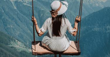 Mulher sentada em balanço no alto de uma montanha