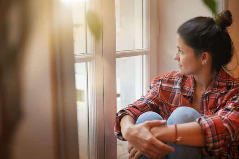 Mulher branca sentada numa janela reflexiva.