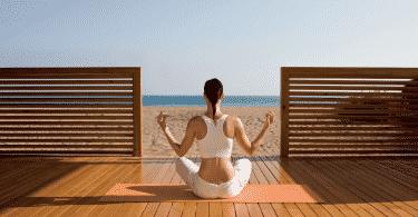 Mulher meditando de frente para a praia