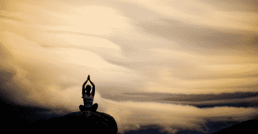 Silhueta de pessoa meditando no topo da montanha