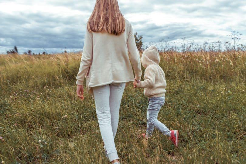 Mulher e criança de mãos dadas andam em campo.