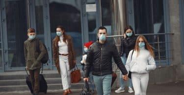 Pessoas de máscara deixam aeroporto.