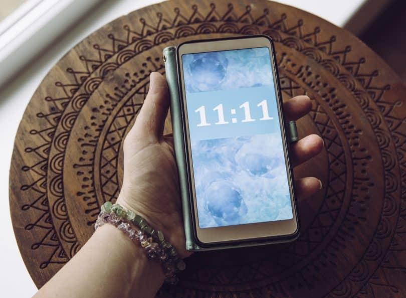 Pessoa olhando o horário 11:11 no celular