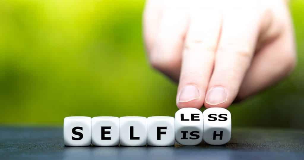 """Pessoa branca virando dados formando as palavras """"selfless"""" e """"selfish""""."""