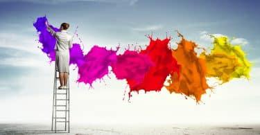 Mulher em escada pinta cenário claro. As manchas de tinta conceituais se espalham pelo cenário.