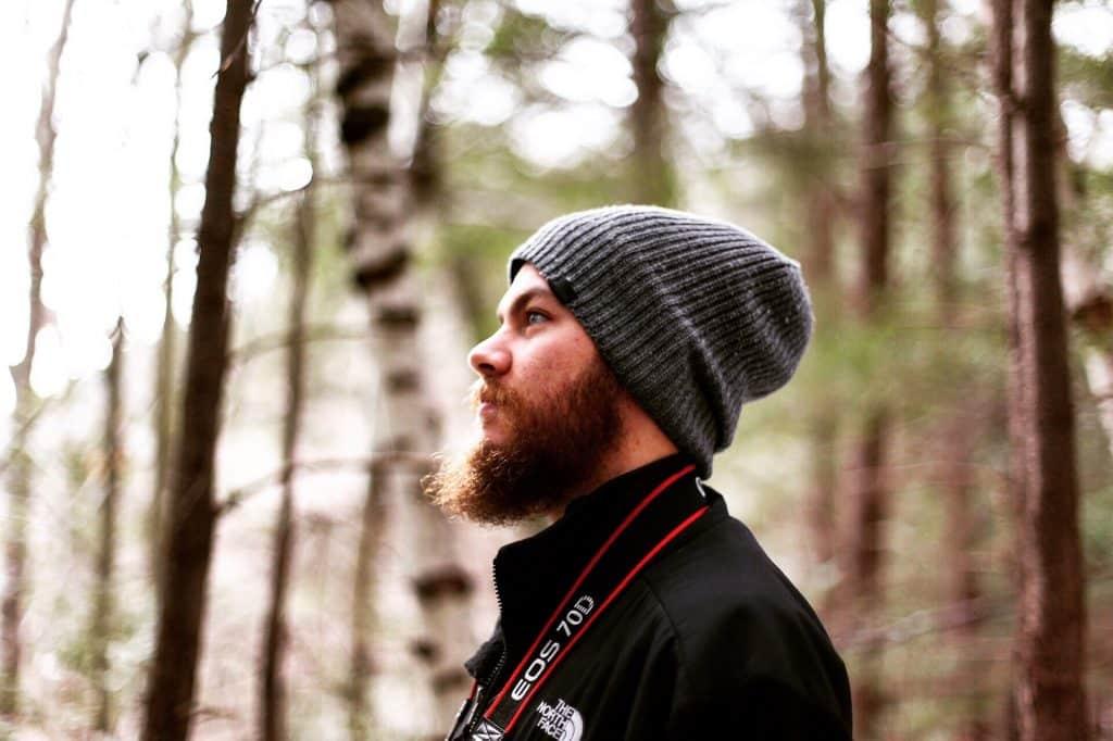 Perfil de homem branco de touca em meio a árvores.