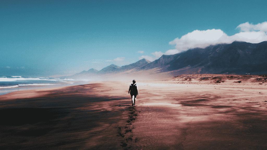 Silhueta de pessoa caminhando na praia